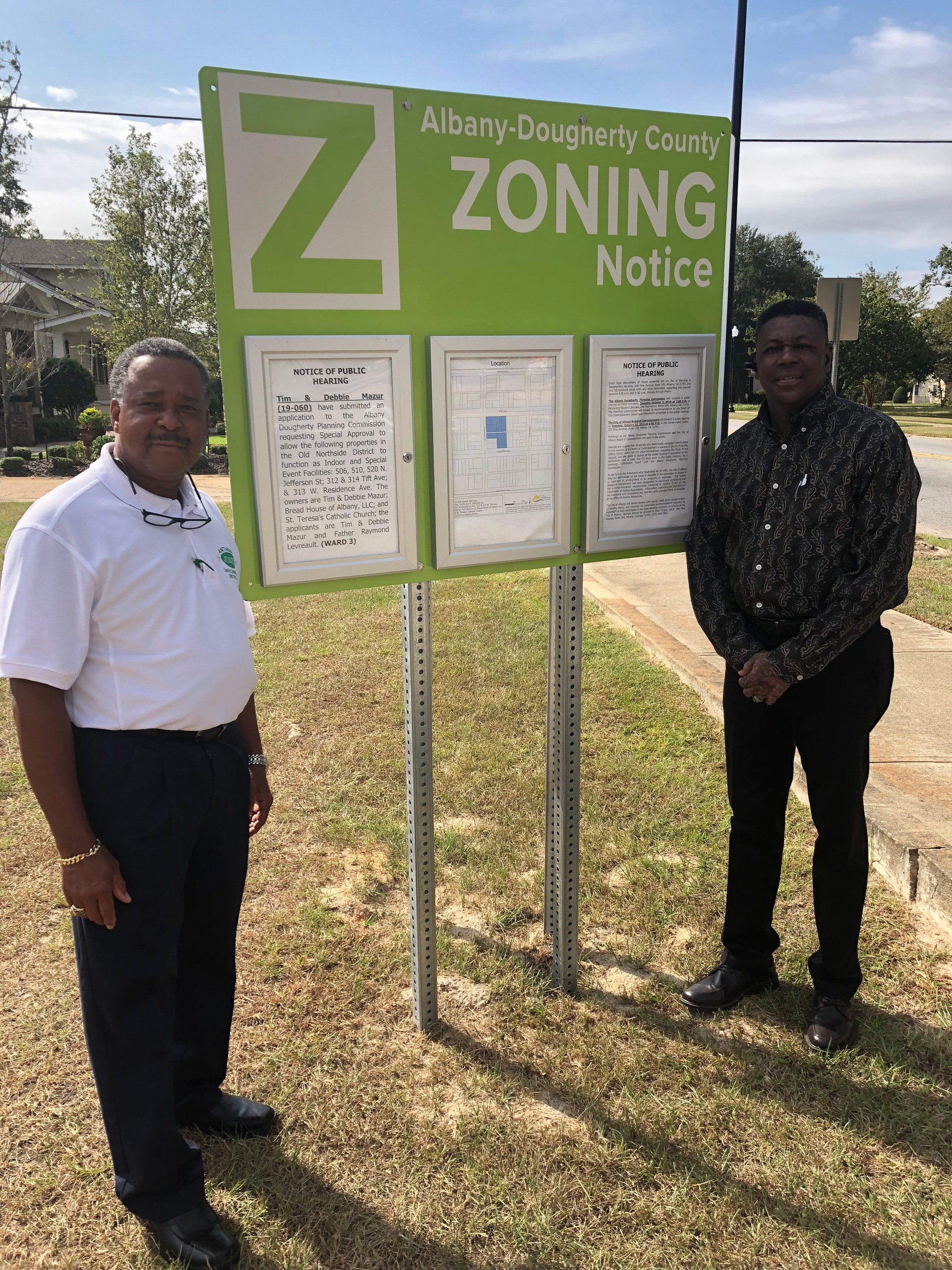 Commissioners standing next to new zoning signage